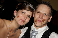 Choc Faces. A wedding couple with chocolate on their faces Royalty Free Stock Photography
