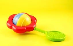 Chocalho colorido do bebê no fundo amarelo Fotos de Stock Royalty Free