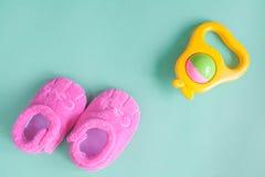 Chocalho e montantes do bebê no fundo verde Foto de Stock Royalty Free