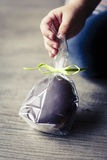 Chocholate and gingerbread easter egg in plastic bags and green ribbon Royalty Free Stock Images