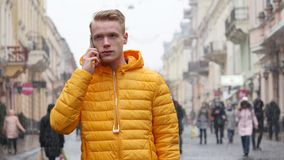 Chocka den unga mannen som talar på telefonen på gatan lager videofilmer