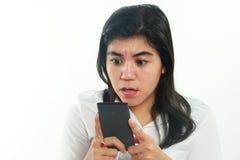 Chockad asiatisk kvinna med hennes smarta telefon Arkivfoto