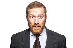 Chockad förvånad affärsman som ser kameran med stora ögon royaltyfri fotografi