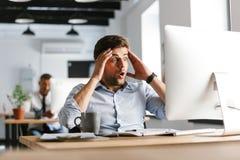 Chockad förvirrad manlig chef som använder compuer, och hållande huvud arkivbild
