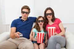 Chockad familj som hemma håller ögonen på filmen 3d Arkivfoton