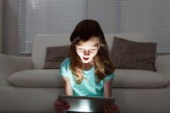 Chockad flicka som använder den digitala minnestavlan Royaltyfria Foton