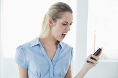 Chockad flott affärskvinna som använder hennes smartphone arkivfoto
