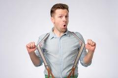 Chockad framsida av den unga europeiska mannen i blå skjorta och hängslen arkivfoto