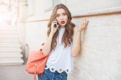 Chockad härlig ung kvinna som utomhus rymmer hennes smartphone royaltyfri foto
