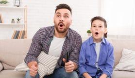 Chockad hållande ögonen på tv för farsa och för son tillsammans royaltyfri fotografi