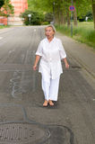 Chockad hög kvinna som går på gatan bara Royaltyfri Foto