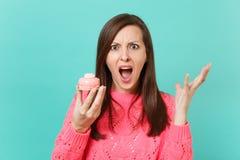 Chockad ilsken ung kvinna i stack fördelande händer för rosa tröja som skriker hållkakan som isoleras på blå väggbakgrund royaltyfri bild