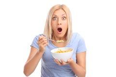 Chockad kvinna som äter sädesslag från en bunke royaltyfria foton