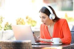 Chockad kvinna som finner massmediaerbjudanden i en b?rbar dator i en st?ng fotografering för bildbyråer