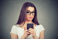 Chockad kvinna som ser hennes mobiltelefon som ser dåliga nyheter eller foto arkivbild