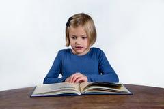 Chockad liten flicka med en bok på en vit bakgrund Arkivfoton