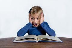 Chockad liten flicka med en bok på en vit bakgrund Arkivfoto