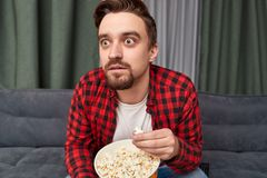 Chockad man som äter popcorn och håller ögonen på film royaltyfria bilder