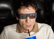 Chockad man som dricker Cola, medan hålla ögonen på filmen 3D Royaltyfria Bilder