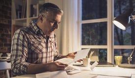 Chockad man som hemma kontrollerar räkningar arkivfoto
