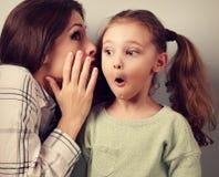 Chockad moder som viskar den hemliga informationen till hennes surprisi Royaltyfri Foto
