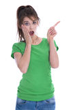 Chockad och häpen ung kvinna i grön skjorta som pekar med henne Royaltyfria Foton