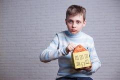 Chockad pojke som knackar till pappleksakhuset Tonårigt och barn p arkivfoton