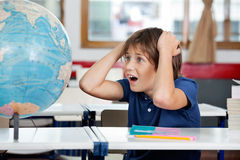 Chockad skolpojke som ser jordklotet i klassrum Arkivfoton