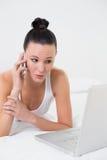 Chockad tillfällig kvinna som använder mobiltelefonen och bärbara datorn i säng Royaltyfri Bild