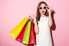 Chockad ung brunettkvinna med shoppingpåsar arkivfoto