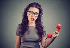 Chockad ung kvinna som ser i telefonlur för misstroinnehavtelefon royaltyfri bild