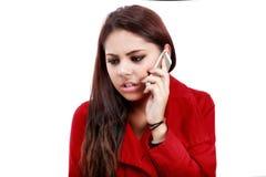 Chockad ung kvinna som ser mobiltelefonen Fotografering för Bildbyråer