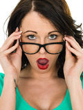 Chockad ung kvinna som ser över hennes exponeringsglas med hennes öppna mun Arkivbild