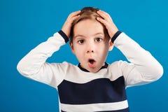 Chockad ung pojke i hållande huvud för tröja arkivbild