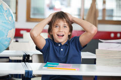 Chockade Little Boy med jordklotet och böcker på skrivbordet royaltyfria bilder