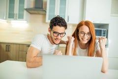 Chockade par som hemma håller ögonen på något på bärbara datorn royaltyfria foton