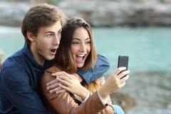 Chockade par som håller ögonen på en smart telefon på ferier Royaltyfri Foto