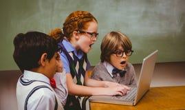 Chockade små skolaungar som använder bärbara datorn Arkivbild