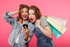 Chockade två kvinnavänner som rymmer shoppingpåsar genom att använda mobiltelefonen Fotografering för Bildbyråer
