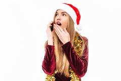 Chockat flicka i den santa hatten som talar känslomässigt på mobiltelefonen royaltyfri foto