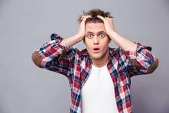 Chockat omtumlat hållande huvud för ung man med båda händer arkivbilder