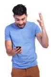 Chockat vid goda nyheter som han läser på telefonen Fotografering för Bildbyråer