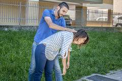 Chocking. Guy making the heimlich maneuver to a girl while she`s chocking Royalty Free Stock Image