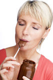 Choco. Young blond woman eating chocolate close up Stock Images
