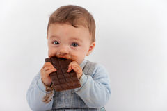 Choco Baby. Adorable baby eating a plate of chocolate Royalty Free Stock Photo