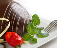 Choco Bomb. Chocolate Bomb Cake on a plate with fork, mint, strawberry and decorative chocolate ribbon Stock Images