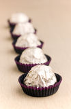 Choco candies in golden foil on table Royalty Free Stock Photo