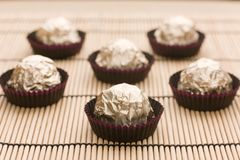 Choco  candies in golden foil on table Royalty Free Stock Photography