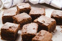 Chocolade brownie gedobbeld het bakken document op houten lijst met een handdoek Stock Foto