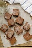 Chocolade brownie gedobbeld het bakken document op houten lijst met een handdoek Stock Afbeelding